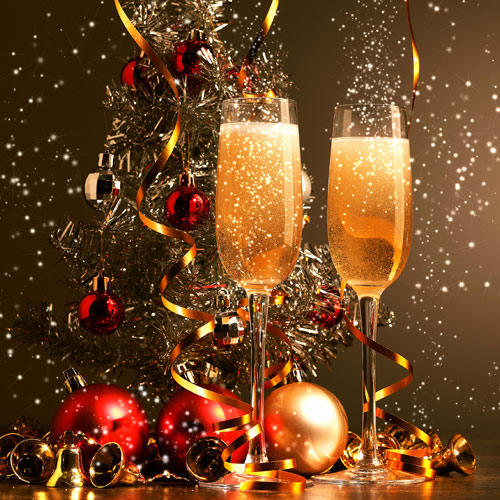 Champagne flutes in front of baubles and Christmas tree